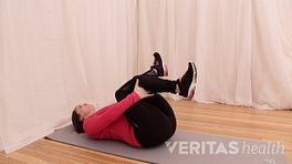 Woman doing a supine piriformis stretch.