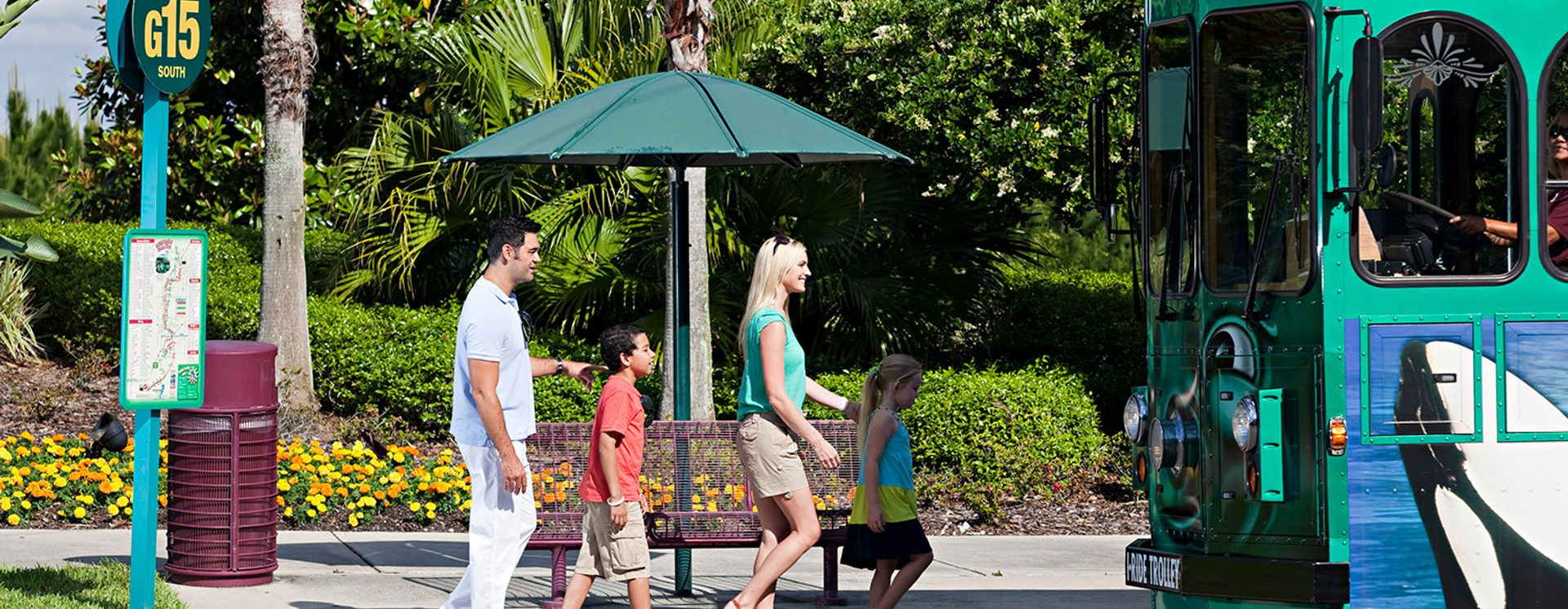 A family at an I-Drive Trolley stop getting ready to board.