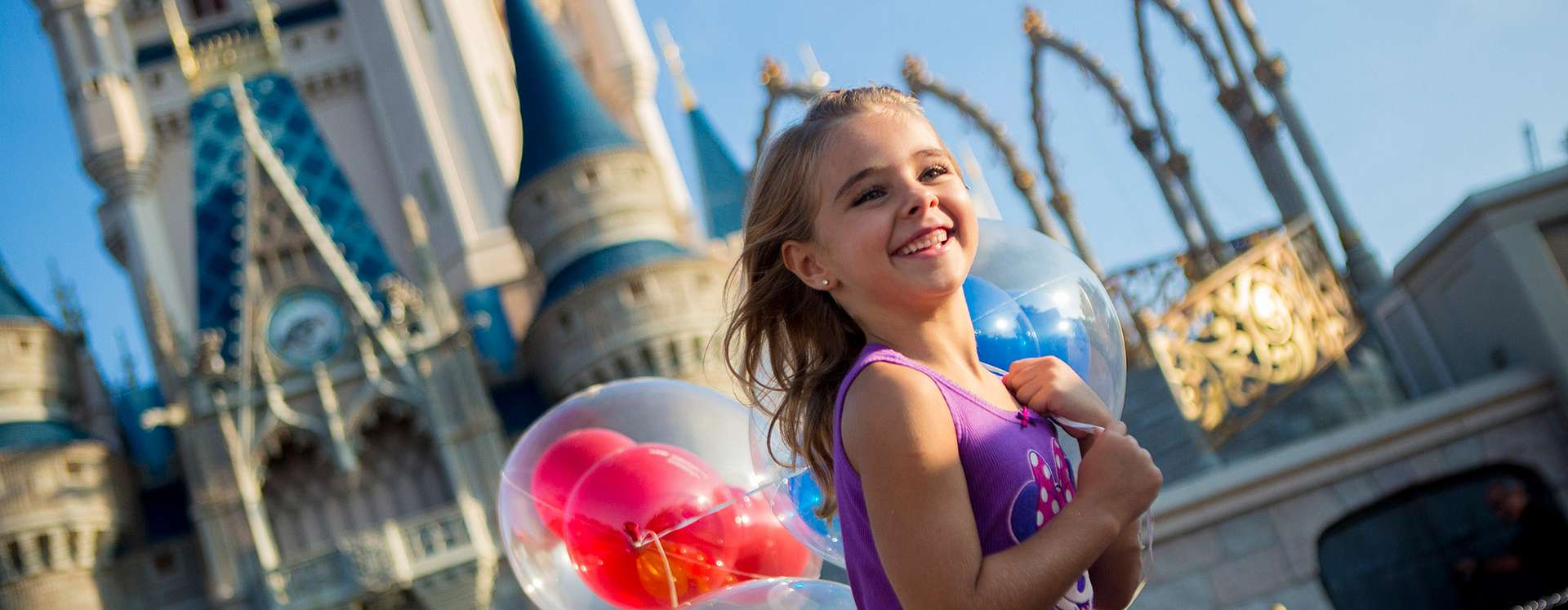 A young girl running with balloons with the castle in the background at Walt Disney World