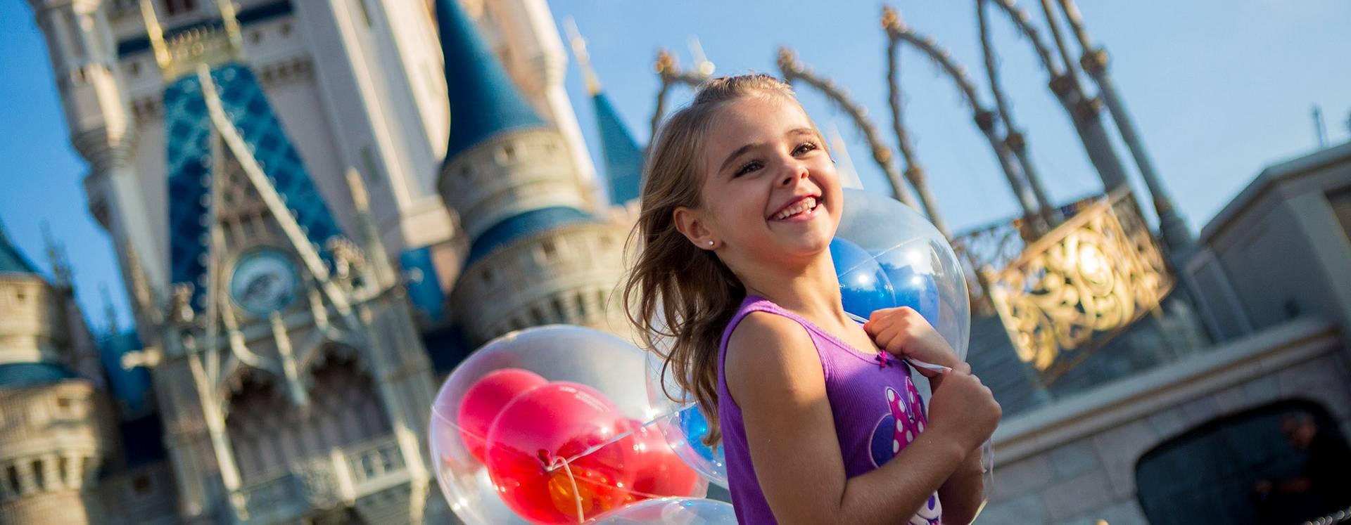 Una niña corre frente al Cinderella Castle con globos de Mickey.