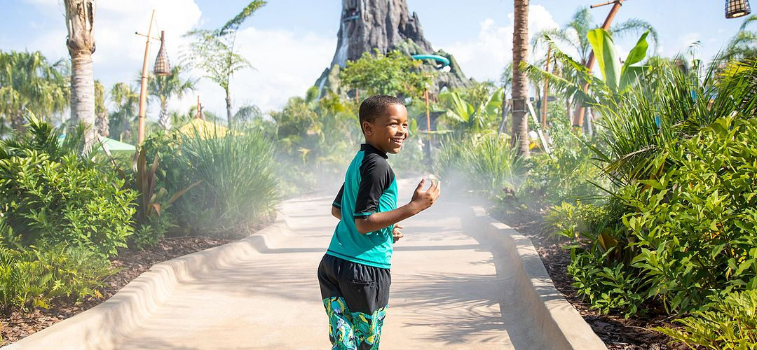 Menino andando na passarela de Honu a atração no vulcão Bay no Universal Orlando Resort