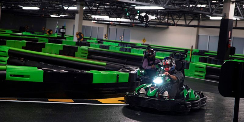 A guy go-karting indoors at Andretti