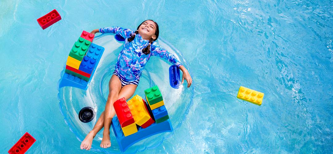 Birds-eye view of a little girl laying on a big floatie in a pool surrounded by Legos.