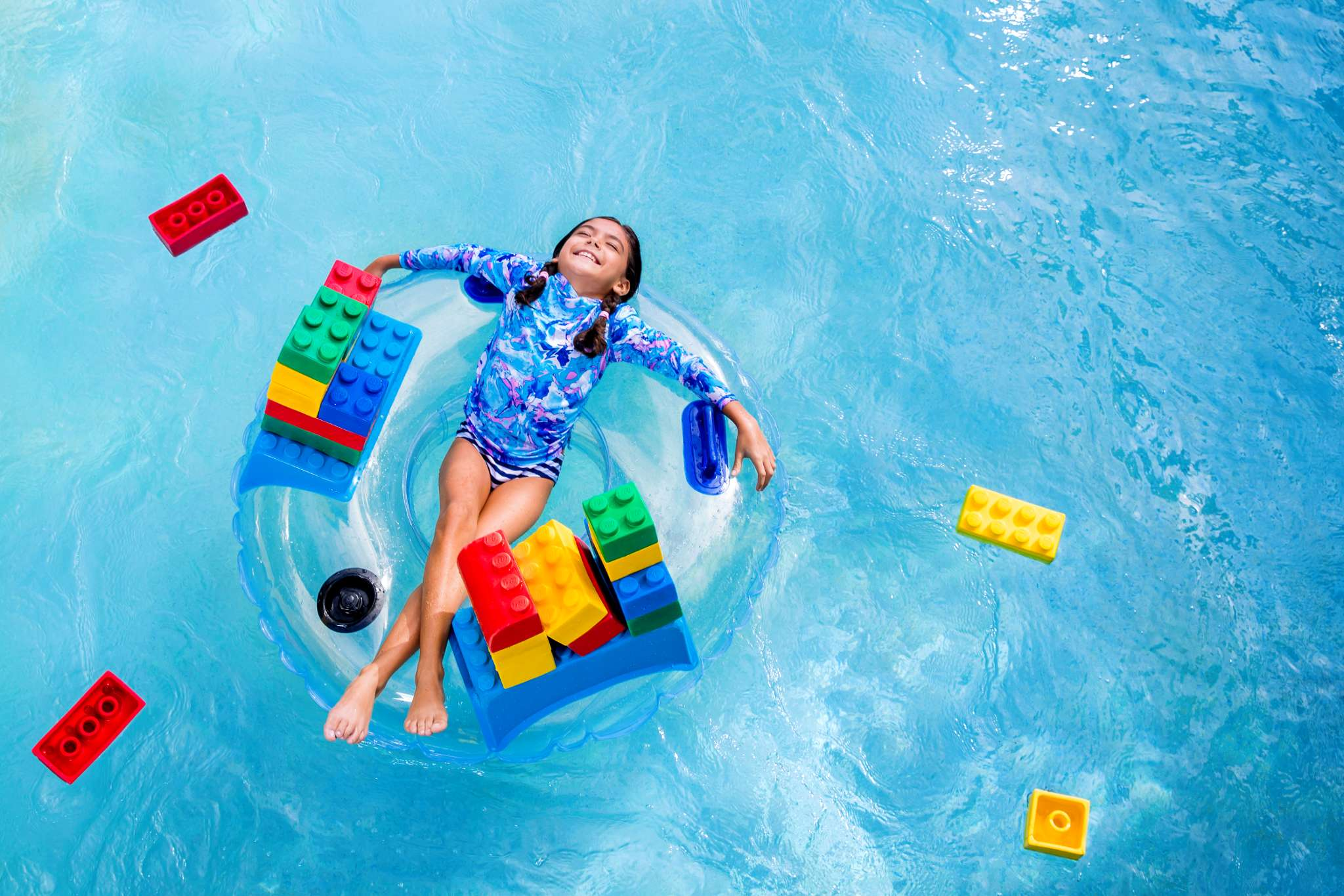 girl floating in a pool with legos floating around her