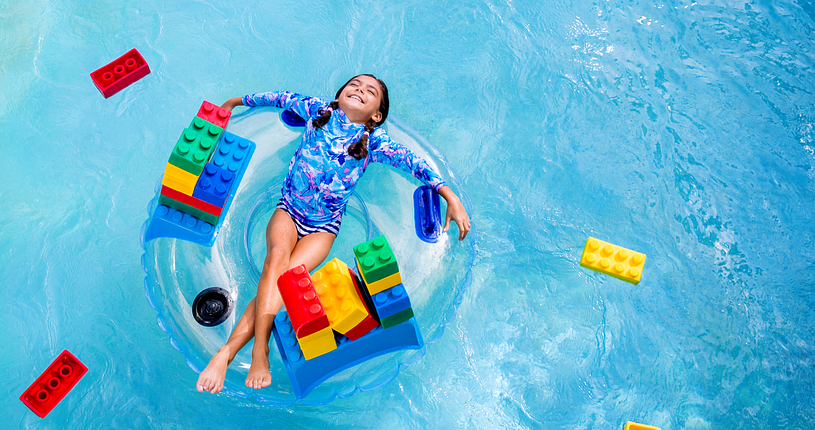 Birds-eye view of a little girl laying on a big floatie in a pool surrounded by legos