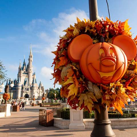 A Halloween wreath featuring a Mickey Mouse jack-o-lantern decorates the lamp posts in the Magic Kingdom at Walt Disney World in Orlando