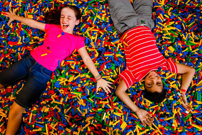 Two kids lying down on top of a piles of legos