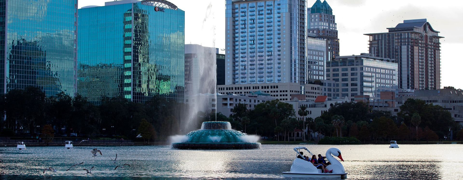 A swan boat and fountain on Lake Eola in downtown Orlando at dusk.