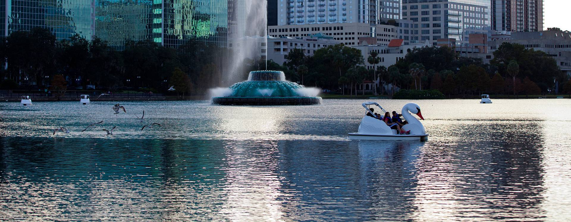 Um barco cisne e uma fonte a Lake Eola em Centro de Orlando, ao entardecer.