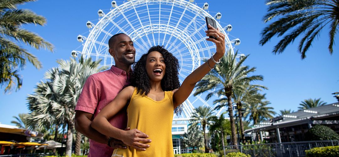 A couple taking a selfie in front of the Wheel at ICON Park.