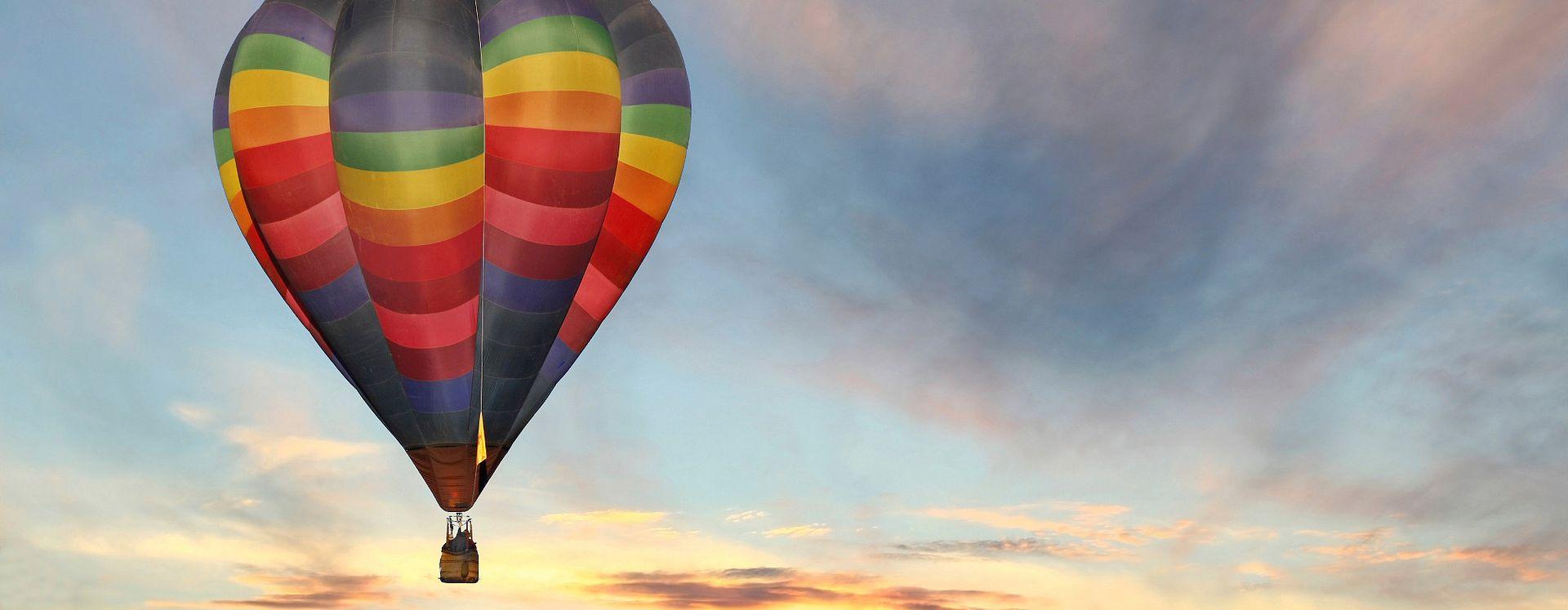 El amanecer hace lucir los colores de un globo aerostático mientras flota en el cielo