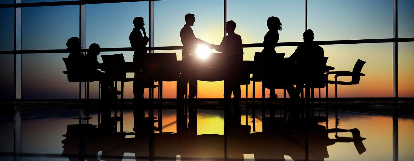 Handshake in office boardroom with sunset in the background