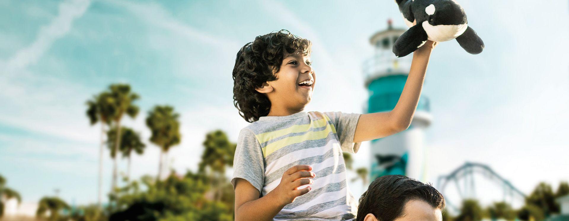 Un niño sentado en los hombros de su papa en Seaworld Orlando, mientras sostiene un peluche de Shamu