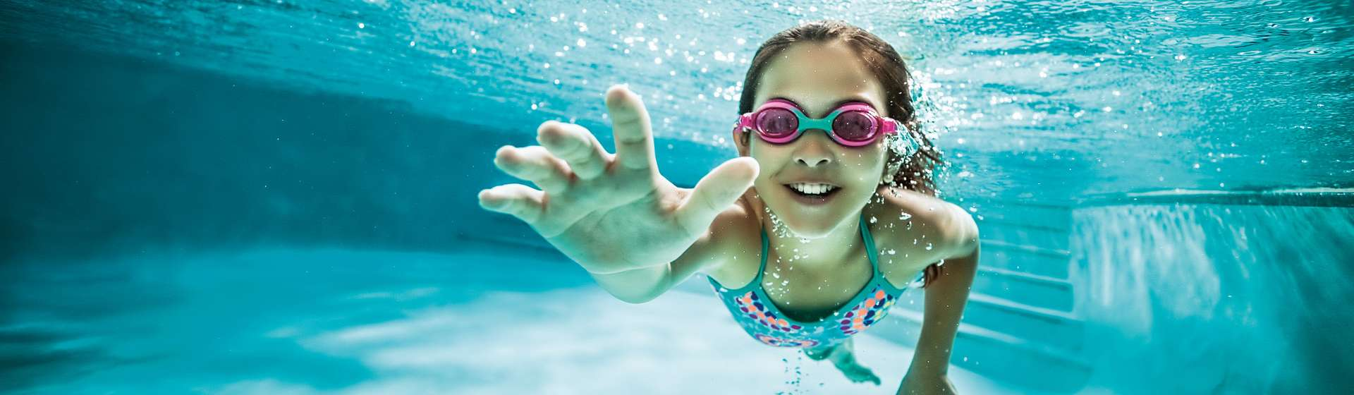 Little girl swimming underwater in a pool.