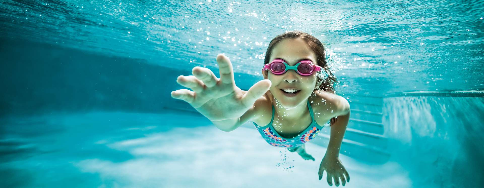 Girl wearing pink goggles and swimming underwater in a pool.