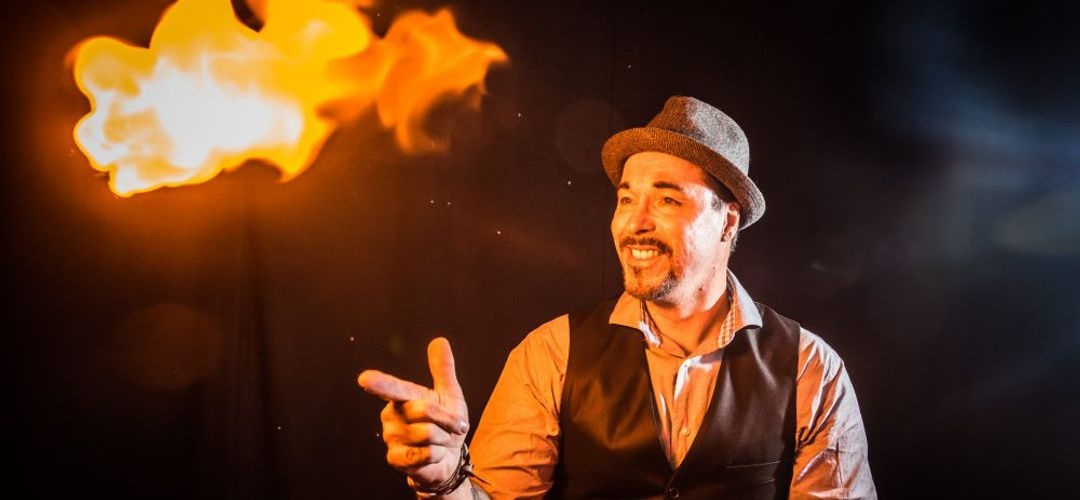 A magician performing a fire trick at the Outta Control Magic Comedy Dinner Show.