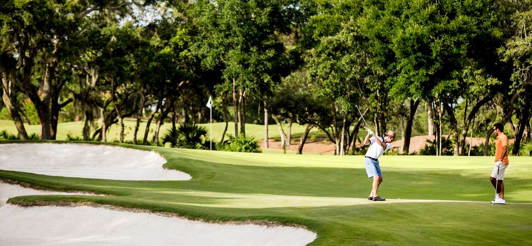 A golf student and instructor playing at the Four Seasons Resort Orlando at Walt Disney World® Resort