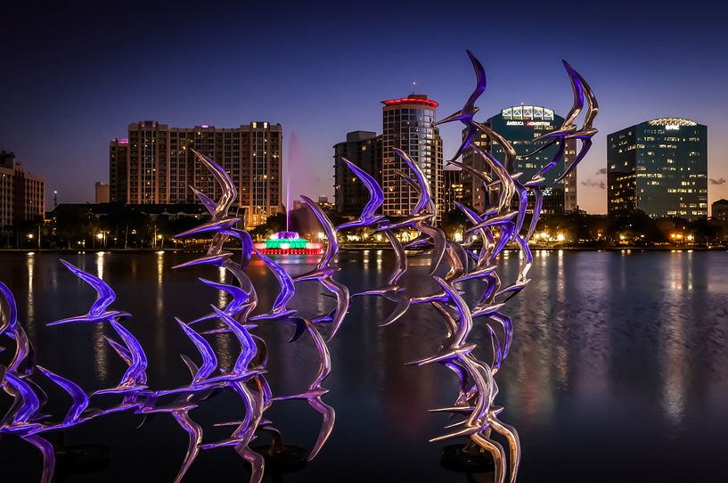 Sculpture of birds in flight with Lake Eola and the Orlando skyline in the background