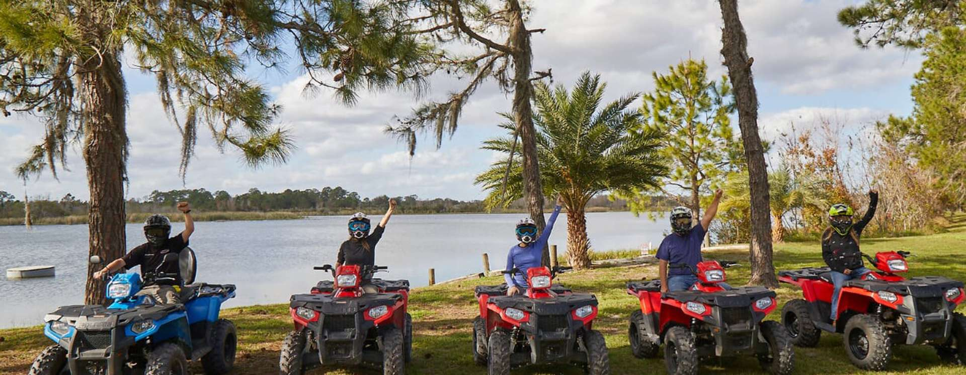 Group of five riders with helmets on ATVs, underneath the shade of pine trees with a lake in the background.