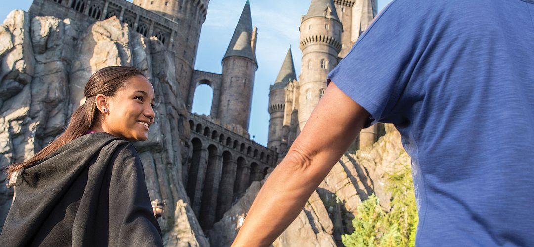 Mãe e filha sorrindo, de mãos dadas, indo para o Hogwarts Castle em Hogsmeade no Universal's Islands of Adventure.