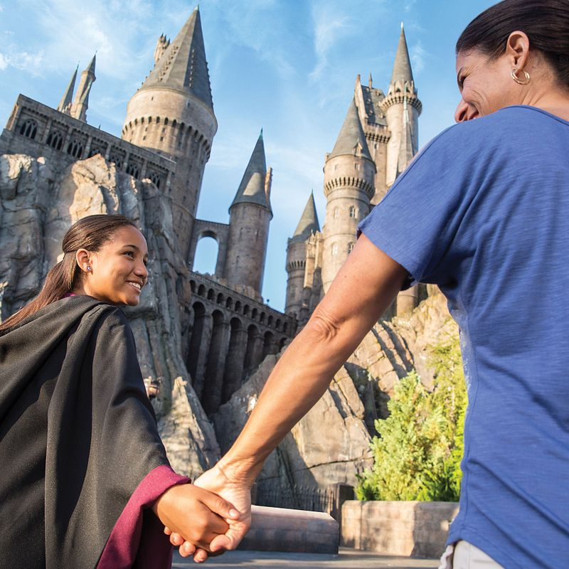 Mother and daughter, smiling, holding hands, and walking to Hogwarts Castle in Hogsmeade at Universal's Islands of Adventure.