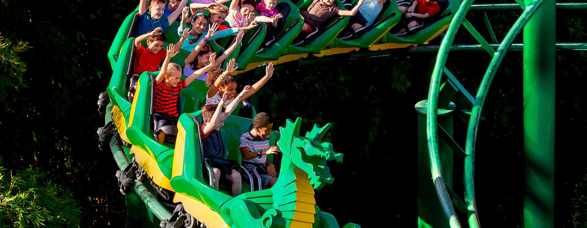 Kids at LEGOLAND Florida Resort theme park riding The Dragon rollercoaster with their arms up in the air.