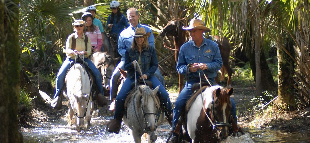 A group of people crossing a stream while horseback riding in Forever Florida tour