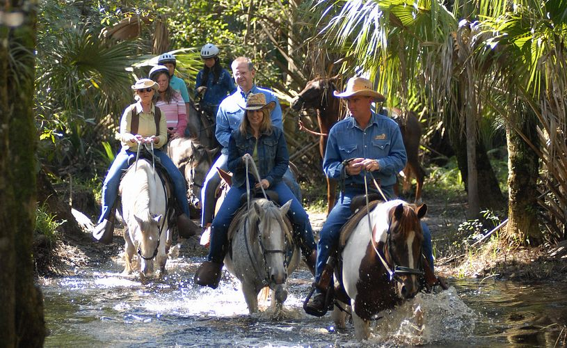 A group of people horseback riding in Forever Florida tour