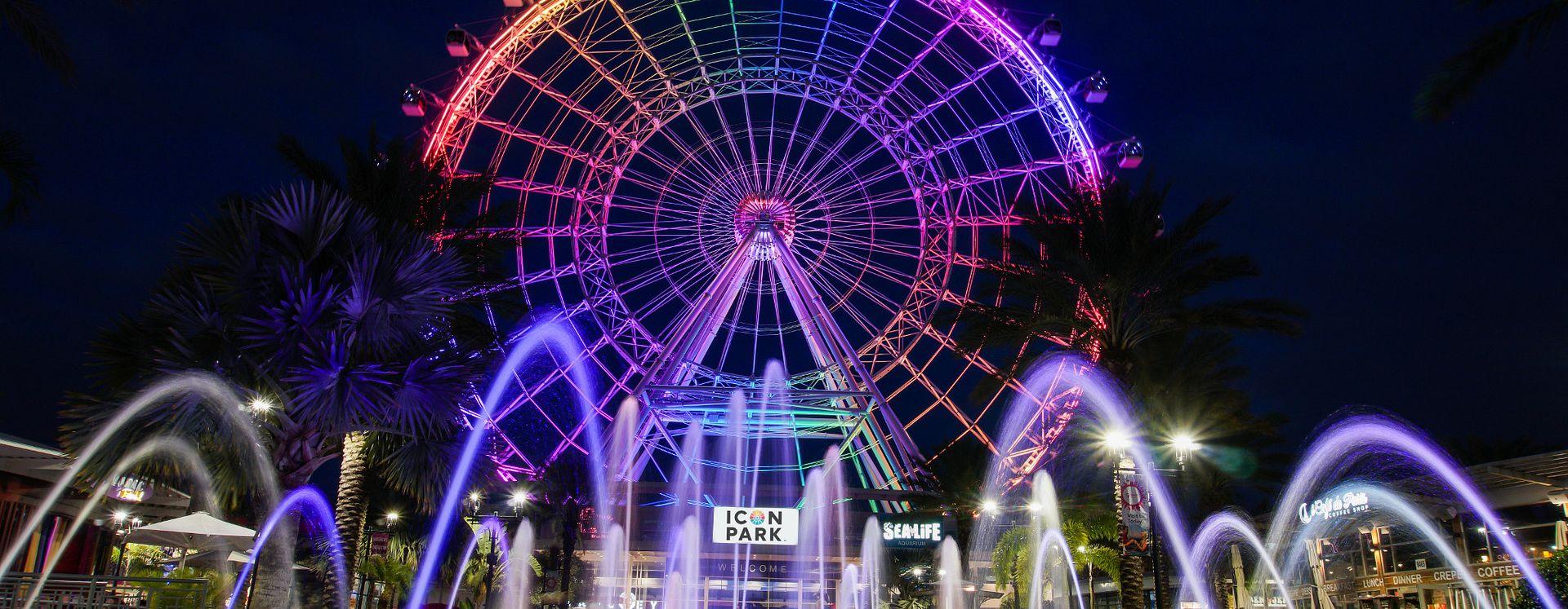 A colorida The Wheel at ICON Park ilumina o céu à noite, com fontes de água em primeiro plano.