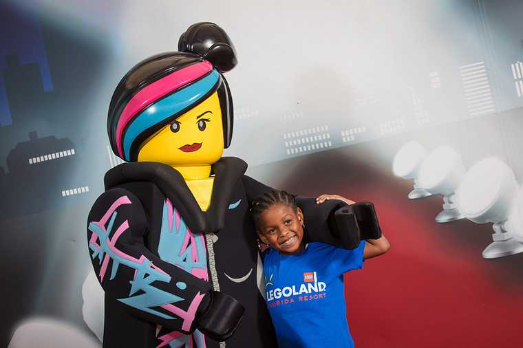 A little girl posing with a LEGO character