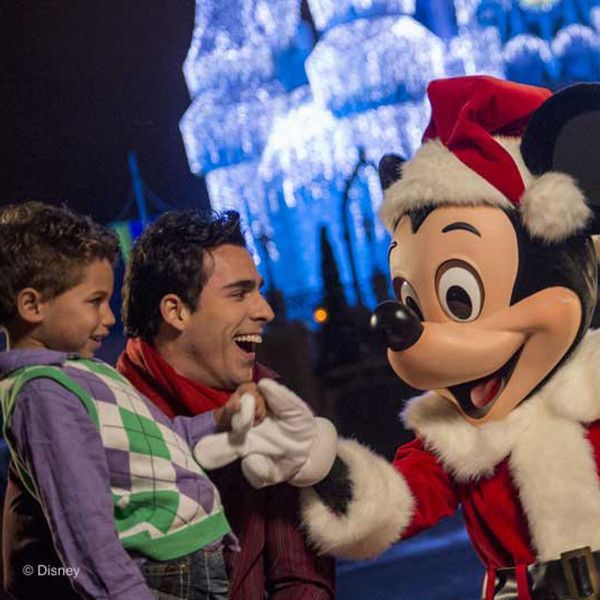 Mickey Mouse greeting guests while dressed like Santa