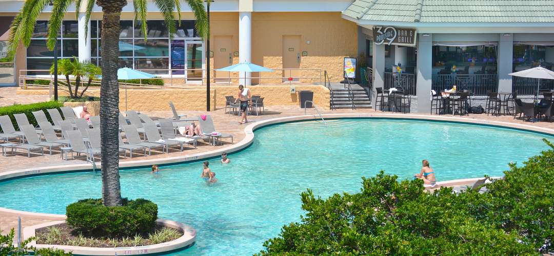 Exterior aerial shot of the pool at Rosen Plaza. Children playing inside the pool and adults lounging nearby on a sunny day in Orlando.