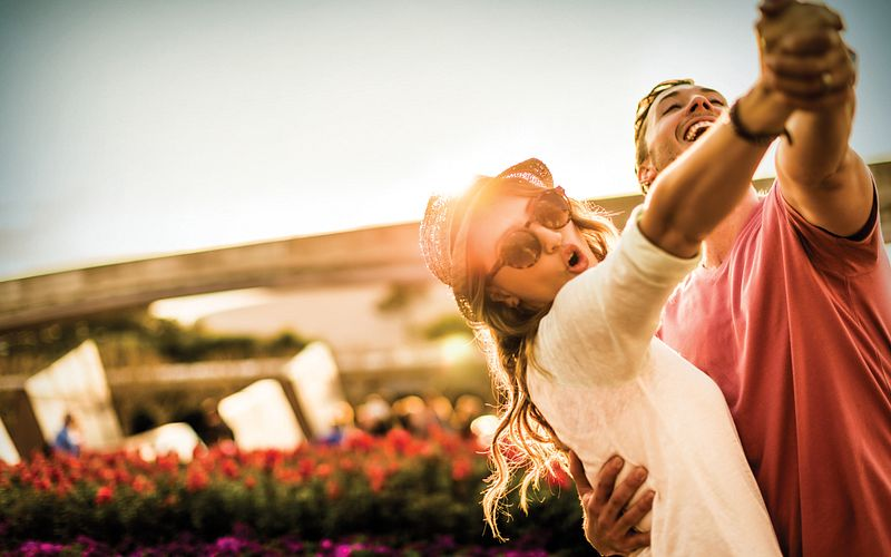 A young couple dancing as the sun sets on a fun-filled day at Epcot.