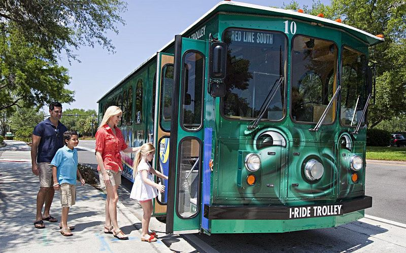 A family of four getting on an I-Ride Trolley bus