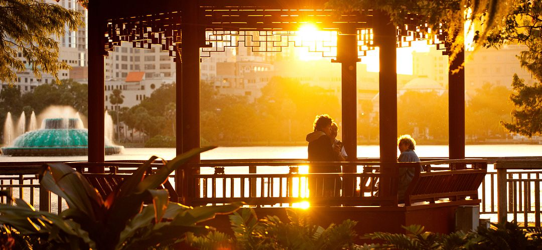 A small group enjoy the sunset from within the Chinese pavilion, or ting, near the water's edge at Lake Eola in downtown Orlando