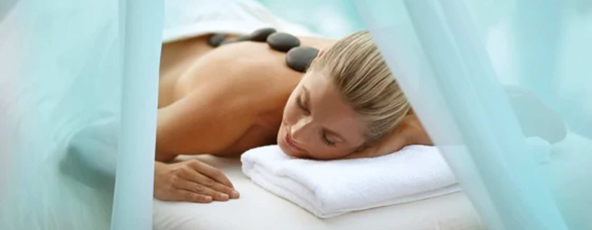 A woman relaxing at a spa while enjoying a hot stone massage