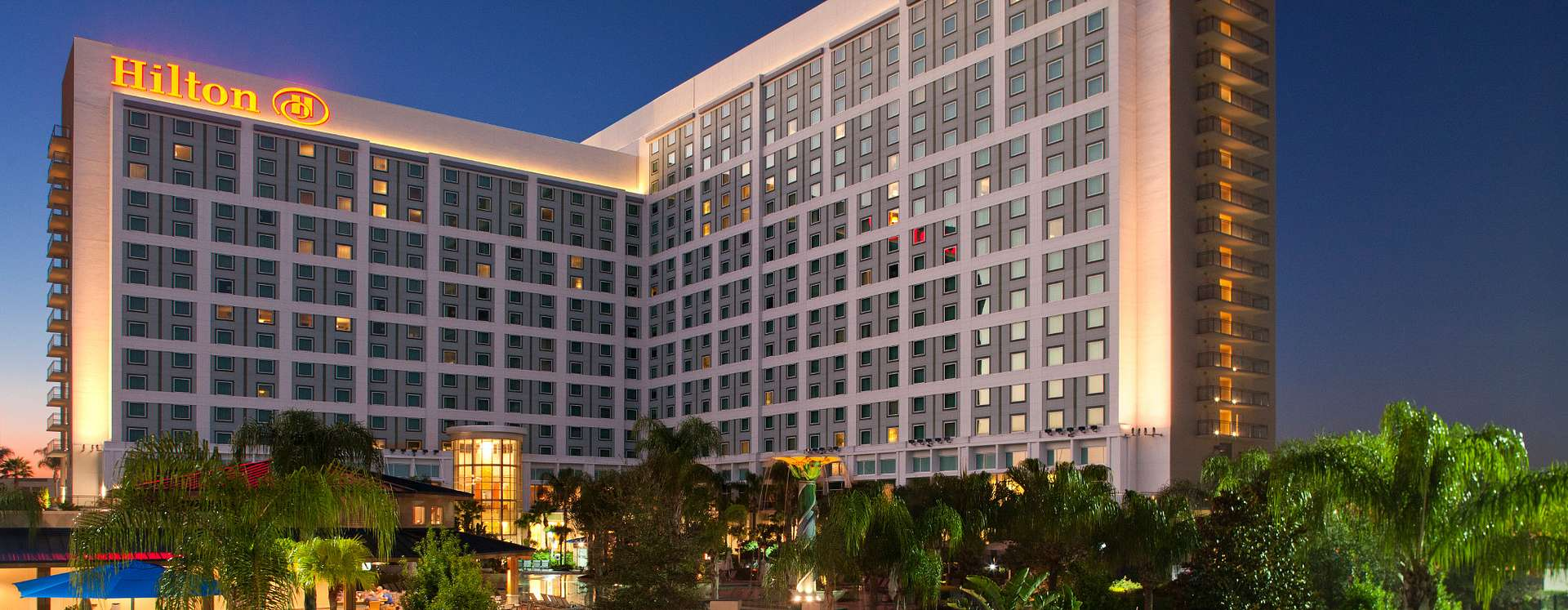 Hilton Orlando hotel exterior at night with the swimming pool in the foreground
