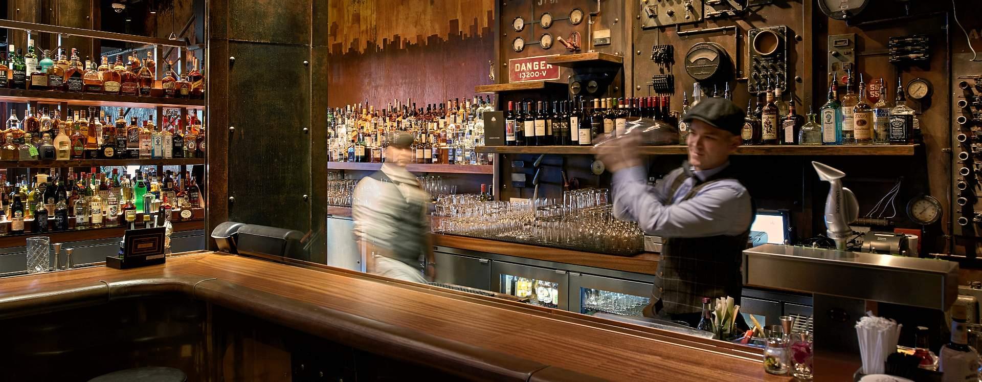 Bartender mixing drinks behind bar at The Edison at Disney Springs