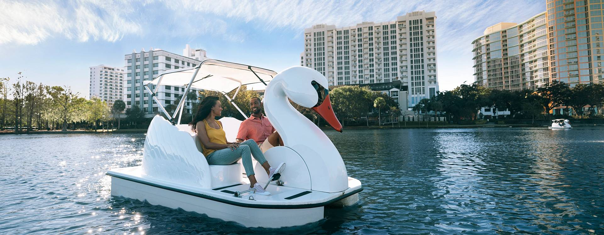 A couple enjoy a swan boat ride on Lake Eola in Orlando, Florida.