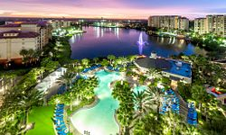 View of the pool and lake at Wyndham Grand Orlando Resort during dusk