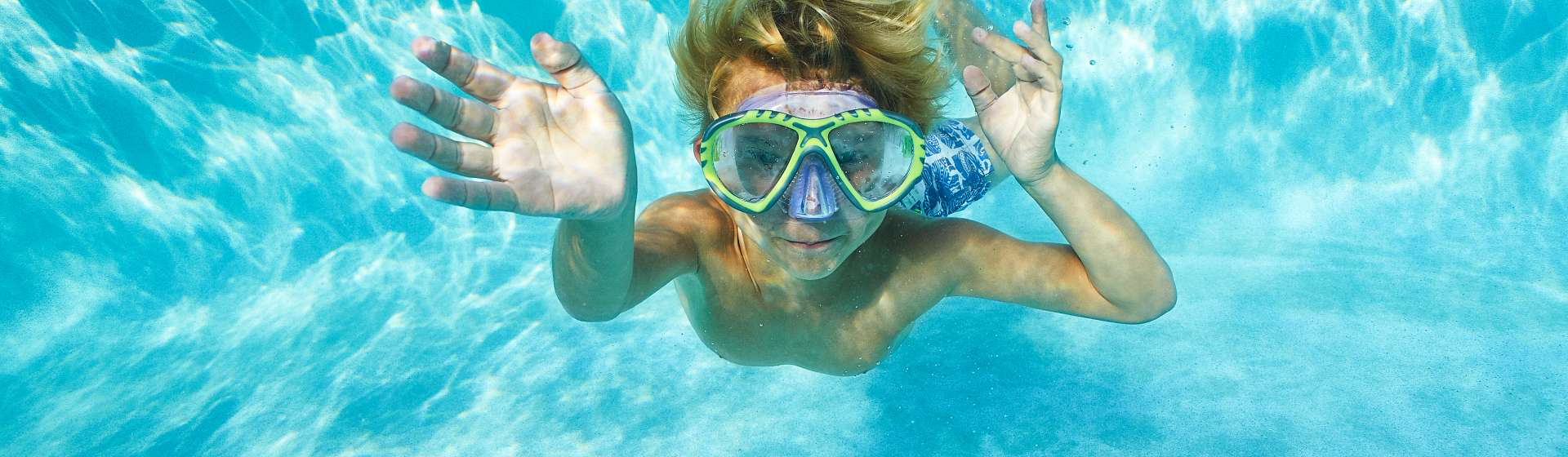 A blonde-haired boy with a snorkeling mask swims underwater in a pool while enjoying a vacation in Orlando.