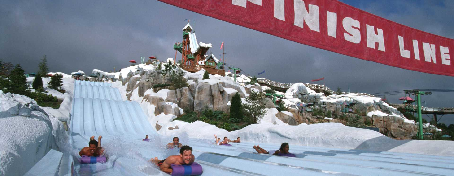 Multiple people sliding down on a race to the finish line of a water slide at Disney's Blizzard Beach