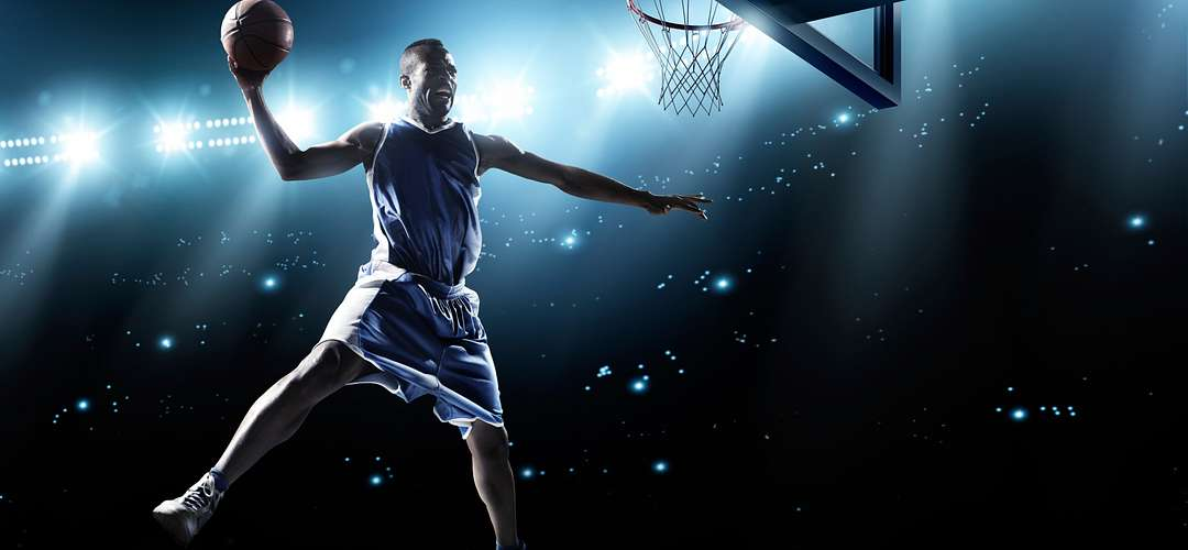 The silhouette of a dunking basketball player against flashing stadium lights
