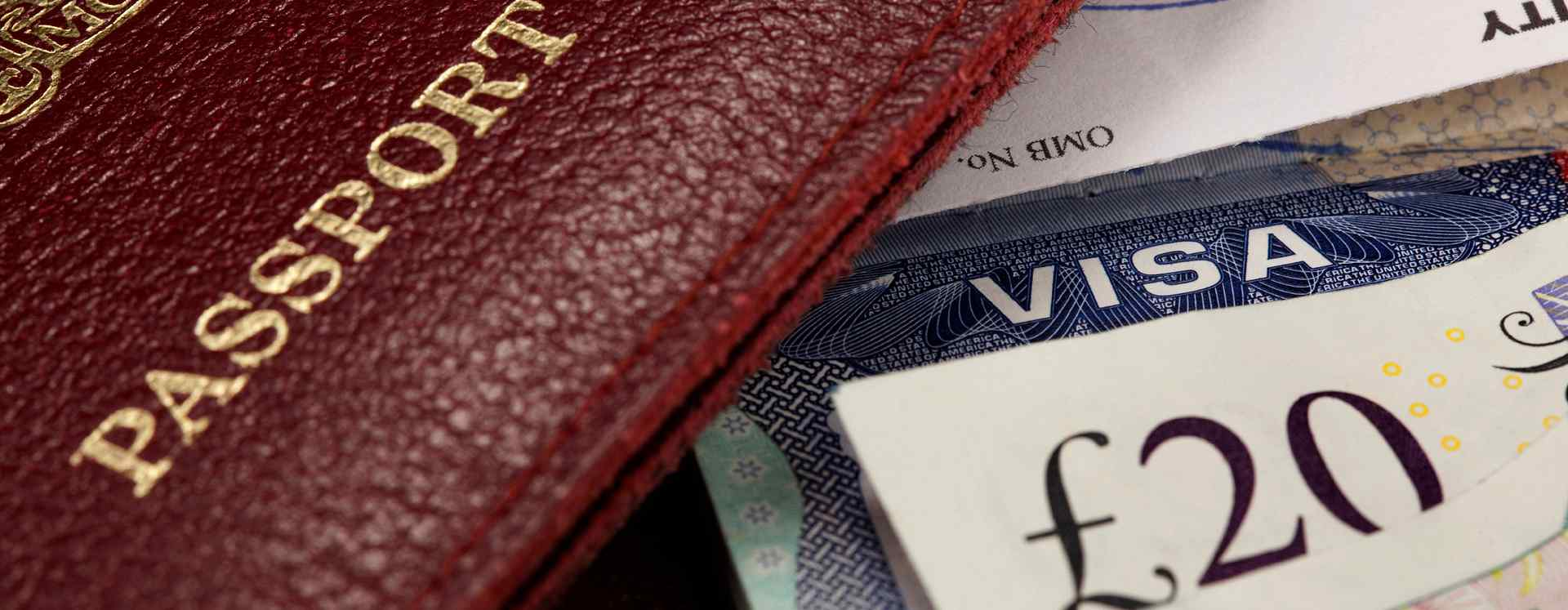 A passport, visa, and money piled on top of each other