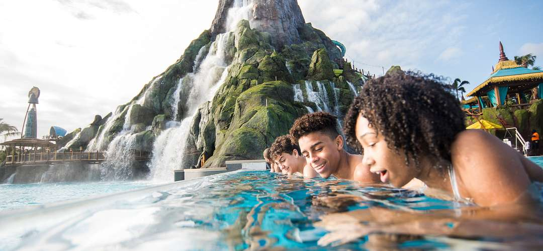 Teens gazing into Reef Leisure Pool with the volcano in the background