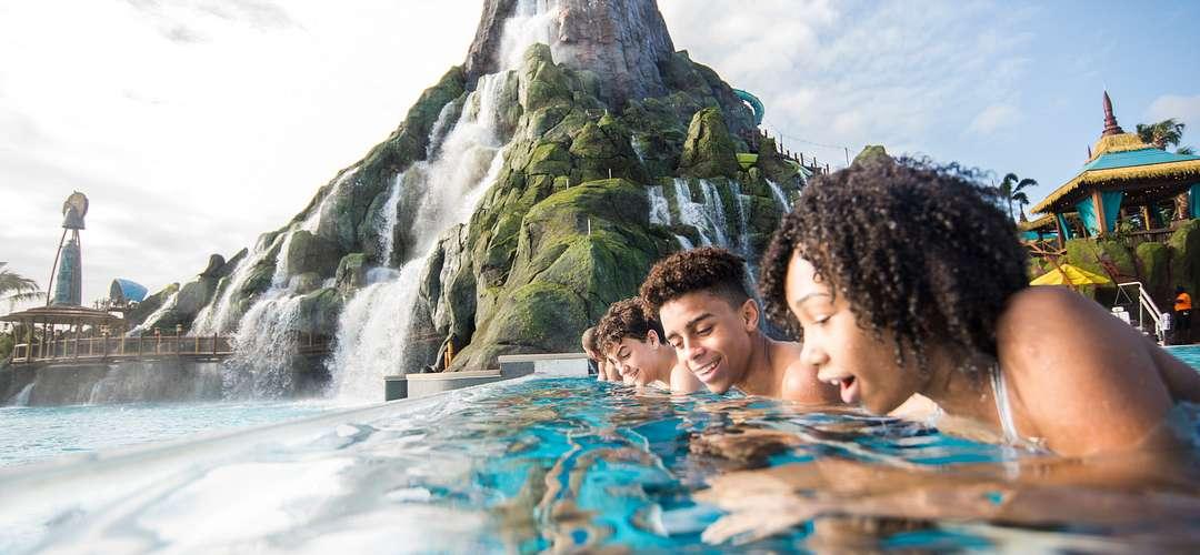 Adolescentes olhando para a Reef Leisure Pool com o vulcão ao fundo.