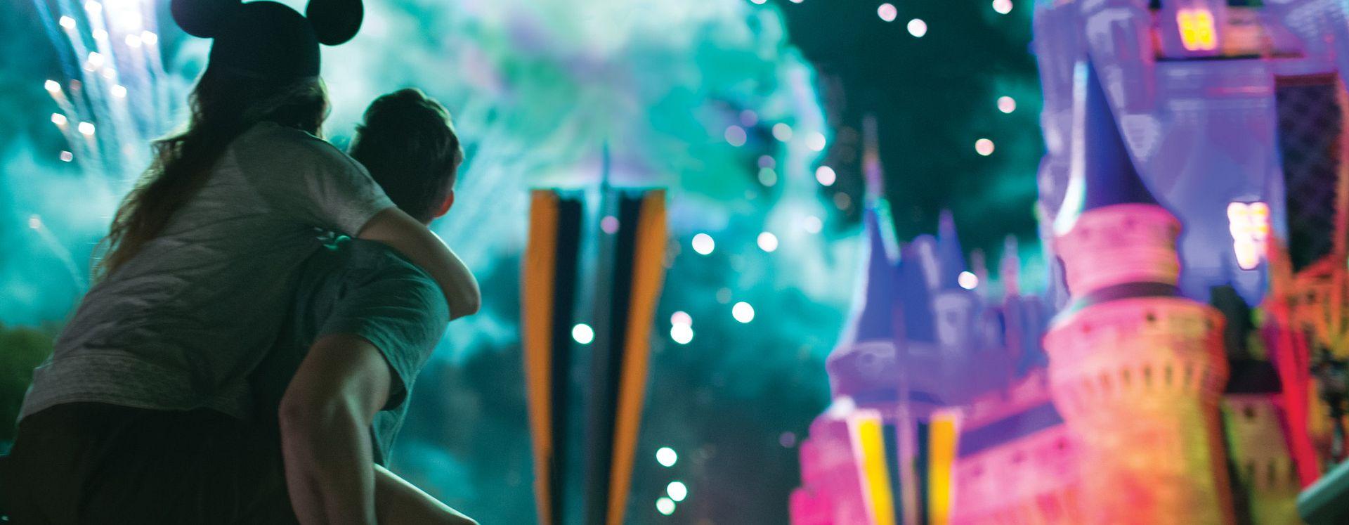 Parkgoers watching spectacular fireworks over Cinderella's Castle at Walt Disney World Resort