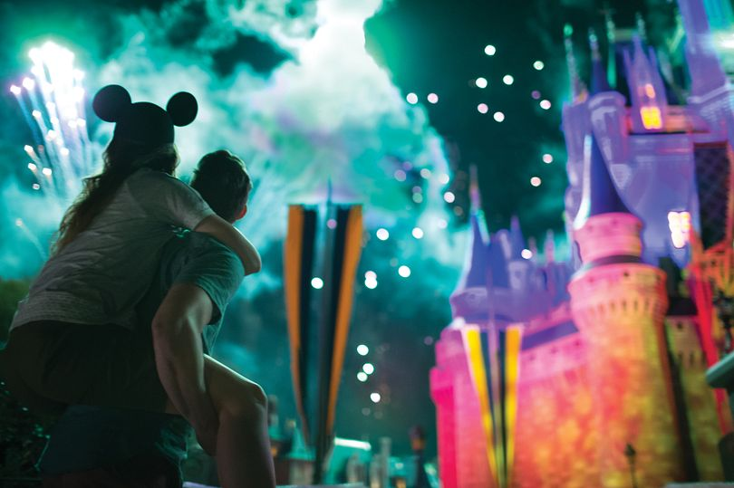 Parkgoers watching spectacular fireworks over Cinderella's Castle at Walt Disney World Resort.