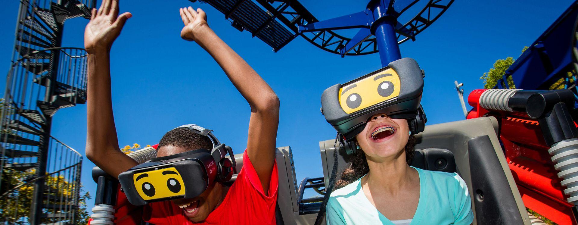 Dos niños en la montaña rusa Great LEGO Race usando equipos de realidad virtual