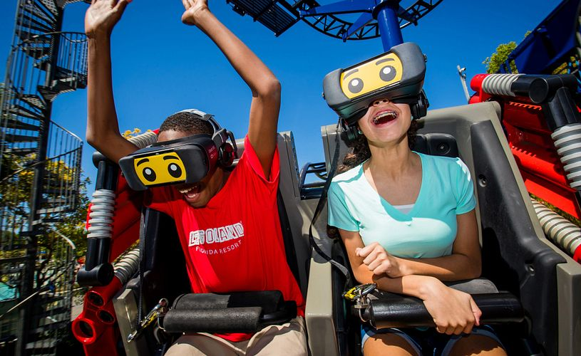 Two kids onthe Great LEGO Race rollercoaster wearing VR sets